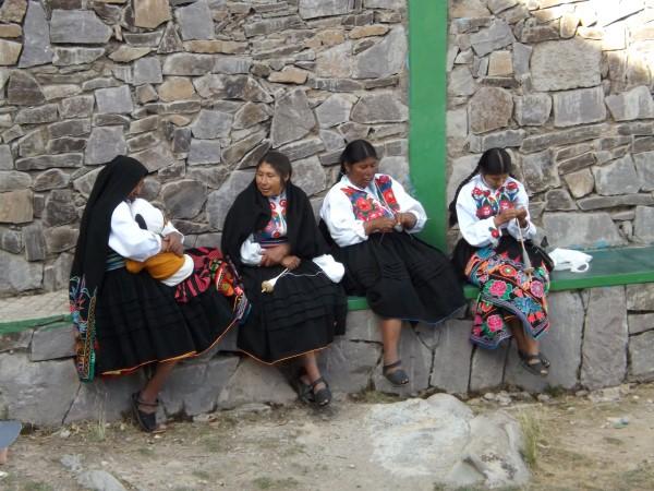 Mujeres hilando en Amantaní con sus trajes típicos